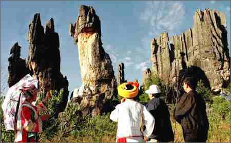 导游阿诗玛(左)在云南省石林风景区乃古石林给游客介绍石林的形成.