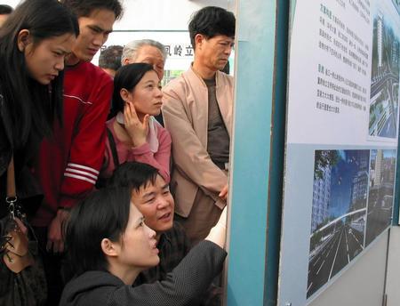 2月22日,南宁市民在认真观看城市规划效果图,仔细对比城市