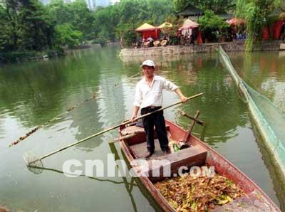 一女子在中山公园游玩时落水,幸被正在水上打捞垃圾的清洁工发现,用竹