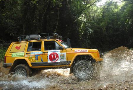 参加穿越的越野车在热带雨林中涉水