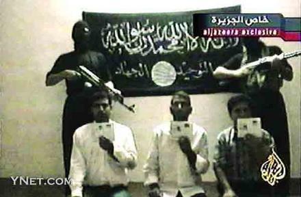图为阿拉伯半岛电视台播出的两名蒙面武装人员押解三名土耳其人的电