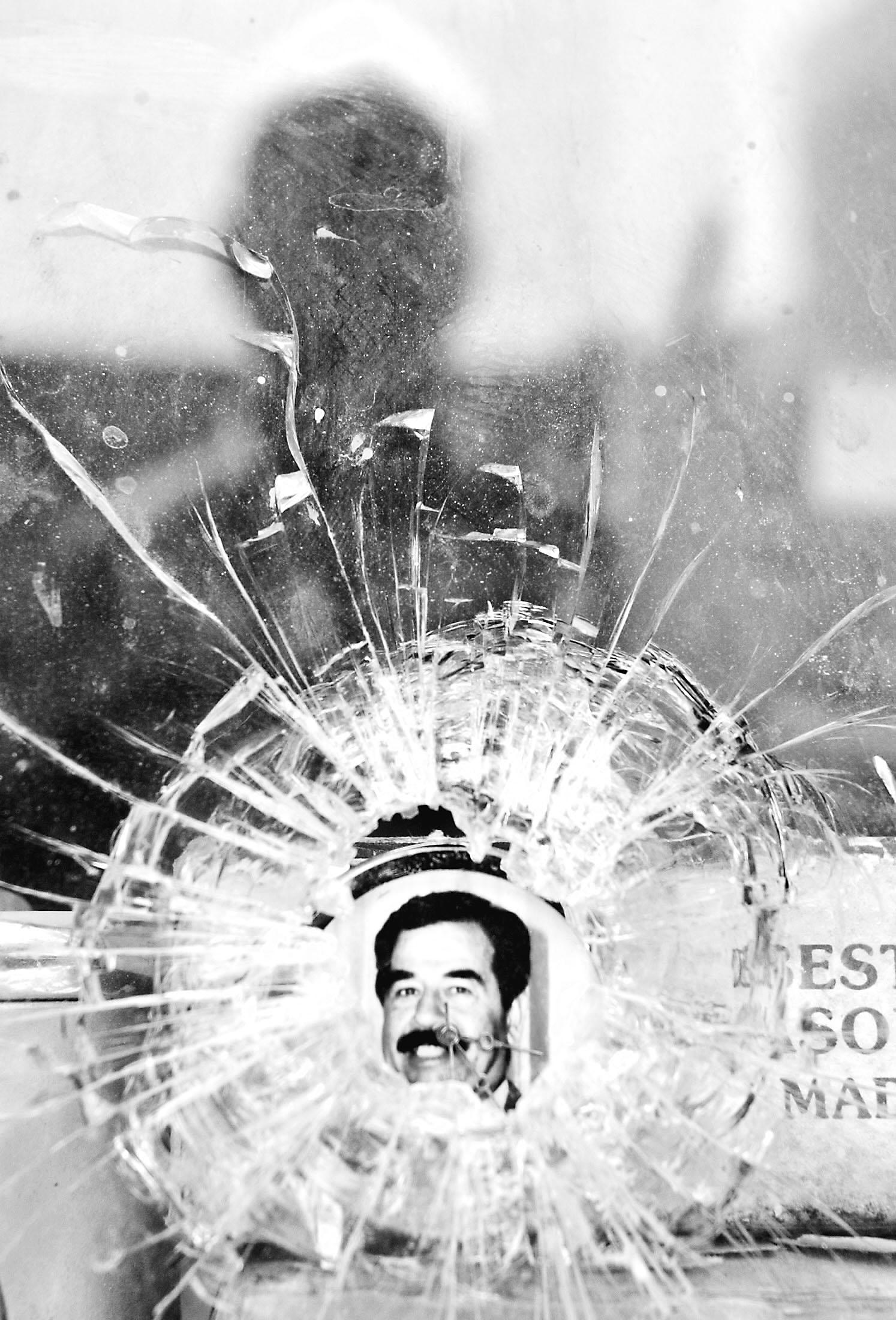6月30日,伊拉克首都巴格达的一家钟表修理店留着弹孔的玻璃后面露出伊拉克前总统萨达姆的头像。 新华社/路透   久违200天,萨达姆6月30日向大家问好。一句早安,是他被移交给伊拉克临时政府时的开场白。   当天的移交仪式没有对外界公开。不过据当时在场的伊拉克官员说,萨达姆侯赛因这位伊拉克前总统、一位执政30余年的统治者当天见到伊拉克人、特别是那些昔日被放逐、今日重新掌权的伊拉克官员时,似乎有许多话想说。   理发剃须消瘦   无论如何,30多年的世事变迁,对于萨达姆来说,岂是三言两语可以