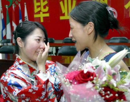7月6日,一名即将从北京第三十九中学毕业的日本学生(左)在和老师告别图片