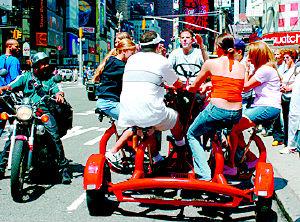 5日,一群年轻人骑着一辆多人脚踏车从美国纽约市的时代广场驶过图片