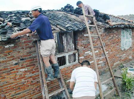 图文:居民在修理被台风损坏的房屋(1)
