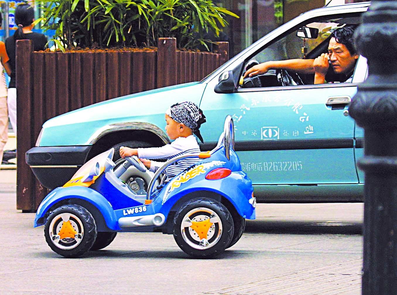儿童驾驶电动玩具车驶上机动车道(图)