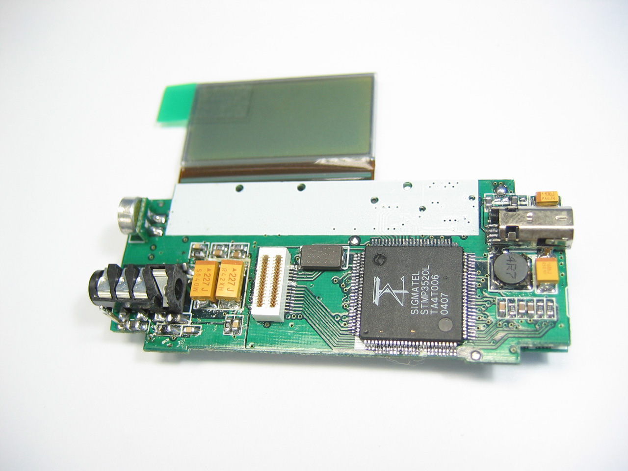 第3页:主电路板设计及解码芯片简介 接下来我们把两块电路模块分开来,分别分析它们的组成结构。首先我们看看主电路板,刚才我们已经知道它的正面主要是LCD液晶屏、五维导航键和FLASH闪存,现在我们来看看它的反面。  从图中可以看到,主电路板反面主要由三步分组成:USB接口电路、解码主芯片及主晶振还有音频输出及录音。解码主芯片是MP3最重要的组成部分之一,就像电脑的CPU、显卡的GPU,直接影响MP3的功能、音质。  解码主芯片有很多种,比较常见的有飞利浦的SAA7750/7751、Telechip的TCC7