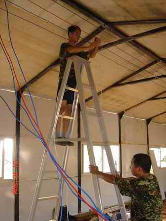 电工在板房房顶与吊顶之间的空间架设电线