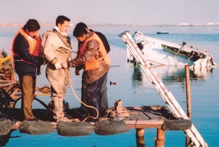 图:潜水员在飞机残骸附近穿戴装备