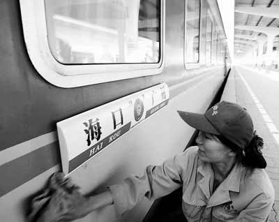 昨日,海口火车站的清洁人员正在为首次跨海列车擦拭车身,首次列车的