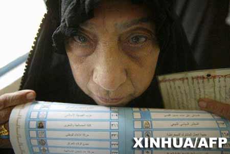 投票 伊拉克/一名伊拉克妇女在萨德尔城一投票站准备投票。