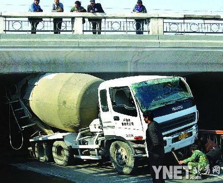 记者赶到现场看到,事故车辆为一白色混凝土搅拌车,正被卡在三环