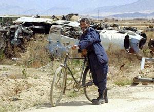 """一名阿富汗人在一架烂飞机前\""""停车思考\"""".多年战争为阿..."""