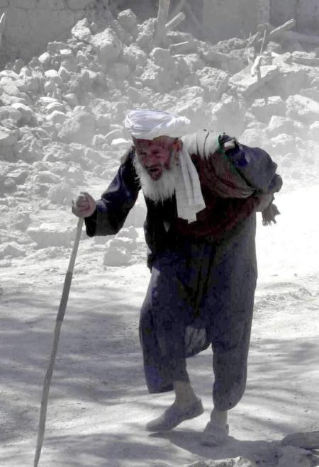 老人马苏德拄着拐杖离开家园