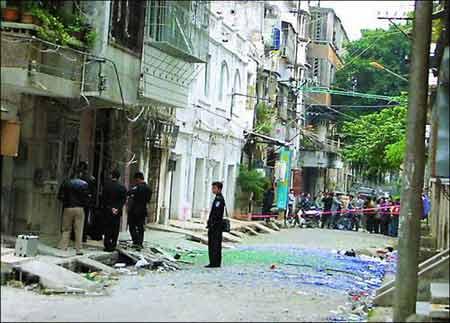 湛江霞山区人民法院附近的一座宿舍被炸得防盗门变形,警方在现场