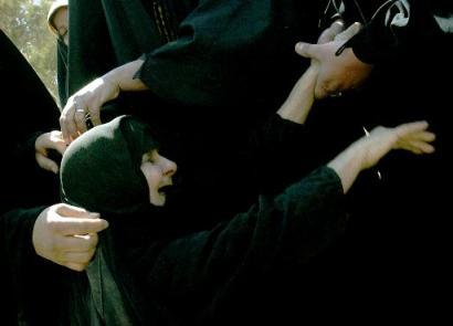 在附近的一座什叶派穆斯林清真寺内,人们站在7具死难者的棺柩旁边