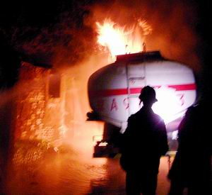 在现场记者看到,起火的院子内还有不少油桶,着火的油罐车还停在