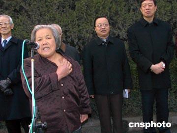 图为南京大屠杀幸存者倪翠萍指着左肩上的枪伤控诉