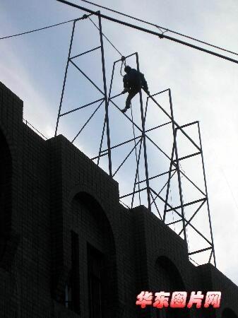 安装工在广告牌的铁架上令观者捏着一把汗.
